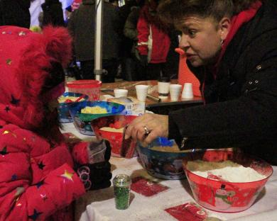 Cynthia Rivera, 6, of Matteson, gets help making reindeer food from Michele Kossak, a volunter at the St. Joseph Youth Group table.