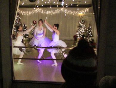 Dancers perform in the American Dance Center on Ridge Road while crowds gather to watch through the studio's display windows.