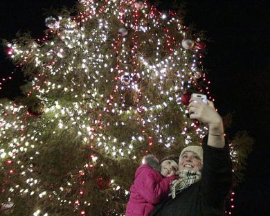 Jennifer Haggerty takes a selfie with her daughter, Vivien, in front of the community Christmas tree at Irwin Park.
