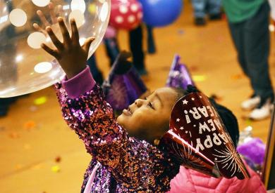 Taigan Harness, 2, tries to catch a balloon during Homewood's annual family Noon Year's Eve party held at the Homewood-Flossmoor Park District Auditorium.
