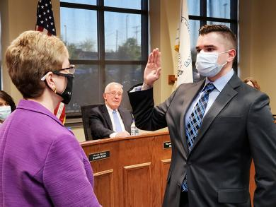 Kyle Rhein, right takes the oath of office as a police officer. (EC)