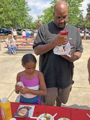 Michael Thompson, of Glenwood, and his daughter, Melissa top their hot dogs.