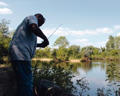 A fisherman removes his catch from the hook on a recent Sunday afternoon.