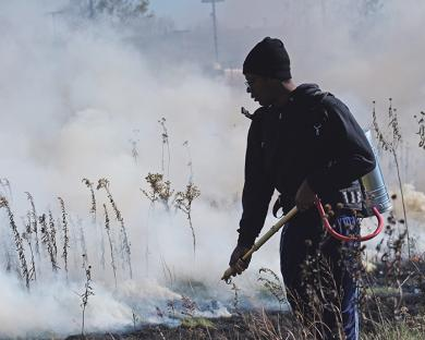 A volunteer works a controlled burn.