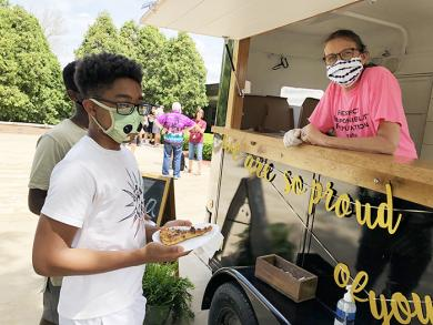 Nona Ridel, secretary at James Hart School, served pizza to Thaddeus Whorton during the Fun and Field Day activity May 21, a day of fun and outdoor activities at the Homewood school. (MT)