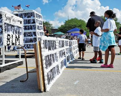 A family views the Say Their Names memorial, which included the names and photos of hundreds of Black people who have been killed by acts of racial violence. (EC)