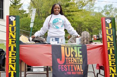 Destiny Watson stands Saturday, May 8, by a booth designed to raise awareness for the inaugural Juneteenth Festival. (BJ)