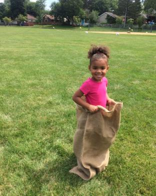 Takaylah Chillis, 3, of East Hazel Crest, gets ready for the sack race that was part of the Homewood Library's party ending the summer reading program.