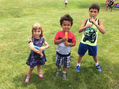 There isn't much that better than a cold treat on a hot day for, from left, Naomi Zurek, Nelson Mahwikizi and Charlie Zurek.