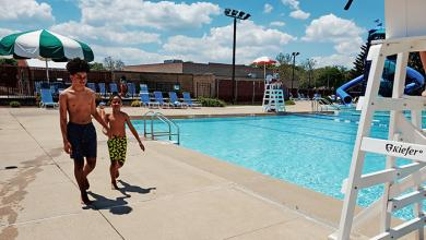 Jukhi Peebles and his brother, Jewelle, head for the water minutes after Lions Pool opened for the season. (EC)