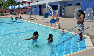 Steven Suggs of Chicago, right, watches children splash during his first visit to Lions Pool. (EC)