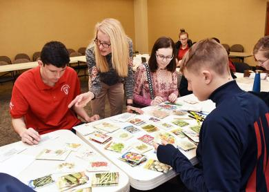Carrie Malfeo, center, shows Charlie Franc from Homewood, left, how to organize smaller seed packets. Also helping at the table are, Cade Noble of Homewood and Hannah Beezie of Flossmoor. Malfeo, who is a member of the Flossmoor Green Commission, helped start the Flossmoor Seed Library, which is hosted by the Flossmoor Public Library.