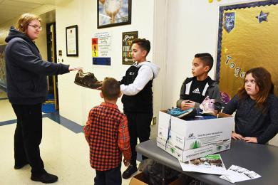 Eric Piros of Homewood and a student at H-F High School, donates his shoes to Sebastian Renko. Volunteering are Tyler Semplinski, Sebastian, Caine Renko and Bella Semplinski at Western Avenue School. Donated shoes will go to the Nike Reuse-a-Shoe program.  Sneakers will be transformed into sports surfaces like running tracks, baseball fields and basketball courts.