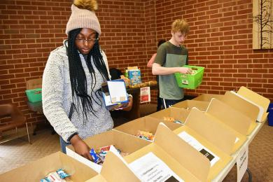 Cailyn Brookens and Steven Hinich, both of Homewood, pack snacks for first responders. The teens, students at H-F High School, volunteered for MLK Day of Service. The event sponsored by PLAN4SUCCESS collected baked goods for local service agencies.