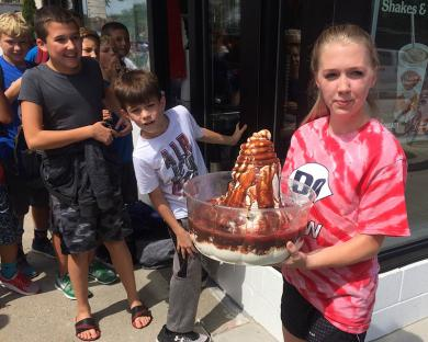 Natalie Hamilton brings out a super-sized sundae for Dairy Queen patrons.