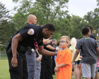 Homewood police officer Ephraim Dorsey offers some advice to his partner prior to the water balloon toss contest at National Night Out in Homewood.