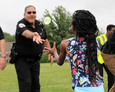 Homewood officer Dave Lux tosses a balloon during National Night Out.