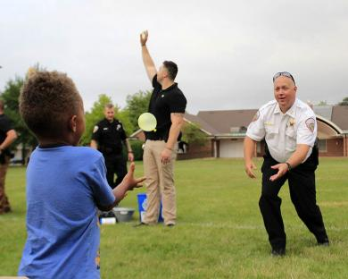 Homewood Deputy Police Chief Rick Sewell tosses a water balloon to his partner.
