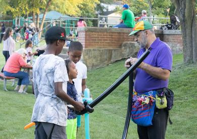 Several youths are excited get balloon swords at National Night Out in Homewood. (QA)