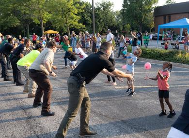Members of Flossmoor's police, fire and public works departments compete in a balloon toss with local kids. (QA)