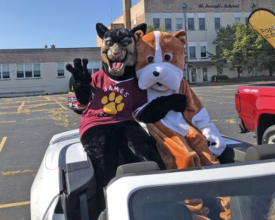 Two of the District 153 mascots — James Hart's panther and Churchill's bulldog — get ready for their drive through Homewood.