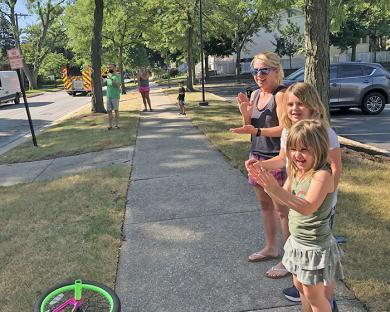 Cheers and waves from Susan Dudik and her daughters Violet, center, a third grader, and Cecilia, a first grader, as the parade went by.
