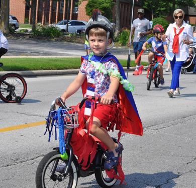 Spencer Janowski, 5 of Flossmoor, heads down Flossmoor Road the morning of Saturday, July 3, during the Flossmoor Volunteer Fire Department Independence Day Parade. (BJ)