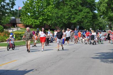 Flossmoor families follow vehicles from the fire department onto Flossmoor Road for the start of the annual parade. (BJ)
