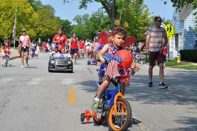 Lázaro Fabian, 6, of Flossmoor, cruises down Flossmoor Road with an outfit and bicycle befitting of the annual Independence Day tradition. (BJ)