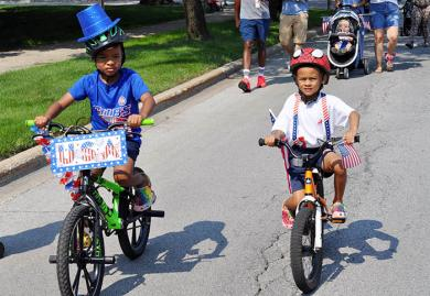 Myles and Mason White, 7 and 5 respectively, of Flossmoor, ride down Flossmoor Road together during the Independence Day bike parade. (BJ)