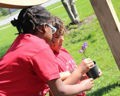 Joy Artis, left, gives Anaya Miller a hand with a young plant.