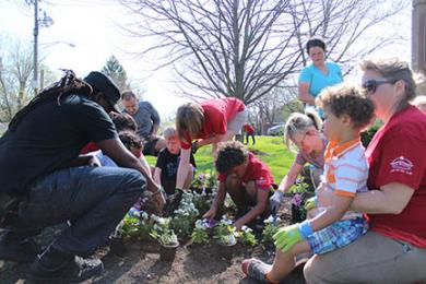 Families with children in Hello Montessori School tend a flower bed in Heritage Park.