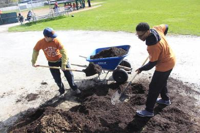 Bart Klicka, left, and Curtis Tillman work together on distributing mulch at Flossmoor Park near the ball fields during Park Pride day. (EC)