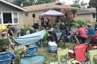 Audience members sit in lawn chairs as Mad Tea performs on Palmer Avenue in Homewood. (NJ)