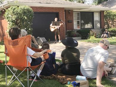 Matthias Gill plays the acoustic guitar and sings in front of a crowd of about 30 onlookers at a home on Dixie Highway (NJ)
