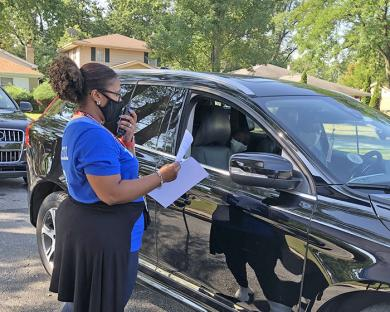 After greeting a parent, Lashone Zinnerman, staff member at Churchill School, radios ahead to fellow staff members who will gather the student's materials.