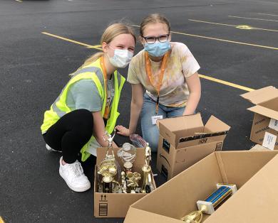 Volunteers Caroline Bivens, left, and Avery Calhoon help sort trophies and other memorabilia. (MT)