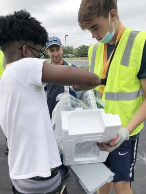 Micah Thomas, left, lends a hand to Declan Dolan as the H-F High students unpack a printer that was donated to Recyclepalooza. (MT)