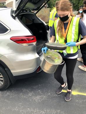 A volunteer carries cookware from a car. These donations will be given to organizations helping those in need or sold to raise money for needy causes. (MT)
