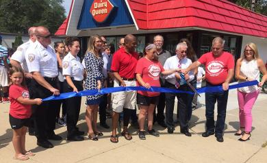 With Kelly Welsh on his right, and Kevin Welsh on his left, Homewood Mayor Richard Hofeld helps cut the ribbon celebrating the reopening of the Dairy Queen on Friday, Aug. 31.