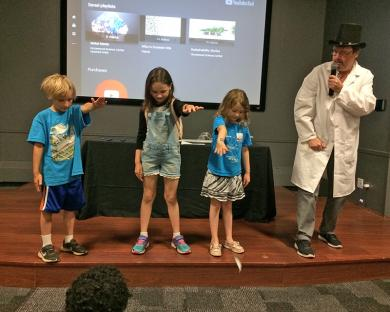Testing a theory about magnetism presented by magician and Governor State University chemistry professor John Sowa, right, children, from left Ezra Raferty, Kayleigh Russell and Claire Kelsven drop magnets and a feather to see which is heavier.