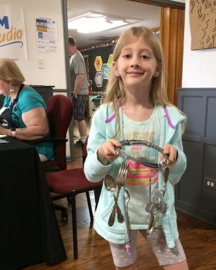 "Brooklynn Roth of Solon, Ohio, visiting her grandparents in Homewood, enjoyed creating a wind chime at the Homewood Science Center's program ""Metal Mania"" on June 9."