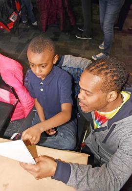 Sherman Adams, right, a teachers aid at Serena Hills school, checks out the roller coaster design by Nathaniel Harris drew. (MC)