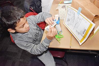 . Isaac Hernandez, a second grader at Serena Hills School, works on building his roller coaster at the Homewood Science Center. (MC)