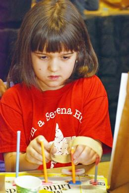 """Addison Huisman, a second grader at Serena Hills, builds a miniature roller coaster during the """"Roller Coasters: An Inventors Journey"""" program at the Science Center in Homewood. (MC)"""