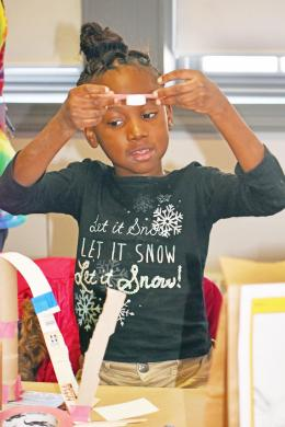 Rickeeler Wilson, a student at Serena Hills school, shows her classmates the miniature roller coaster she built using recyclable materials. (MC)