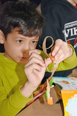 Ulises Salcedo tears his paper just right as he makes a miniature roller coaster at the Science Center located in Homewood. (MC)