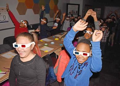 Wearing 3D glasses, Serena Hills second graders Aemilia Miranda, Saya Knazze and their classmates feel like they are taking a trip on a roller coaster while watching a video at Homewood's Science Center's Michael Wexler Theater. (MC)
