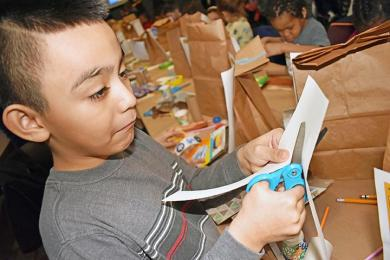 Christopher Munoz-Hidalgo cuts paper out to design his miniature roller coaster at Homewood Science Center in Homewood. (MC)