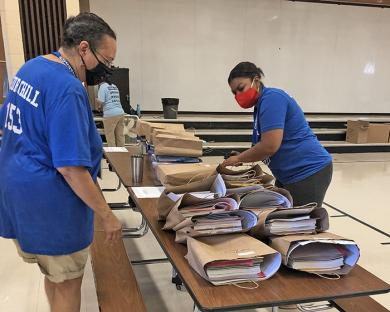 Staff at Churchill School go through sorted materials for third, fourth and fifth graders. Parents did a drive-thru Thursday to collect the bag of supplies.